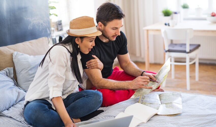 Young mixed ethnicity couple sitting on bed with laptop, looking at map and planning trip.