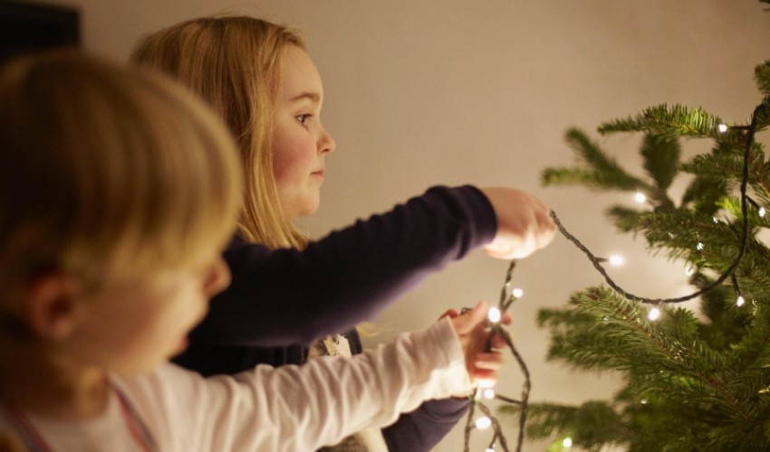 Young children stringing lights on a Christmas tree.