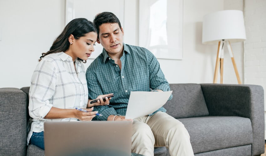 Young couple sitting on couch looking at finances with calculator, laptop and spreadsheet.