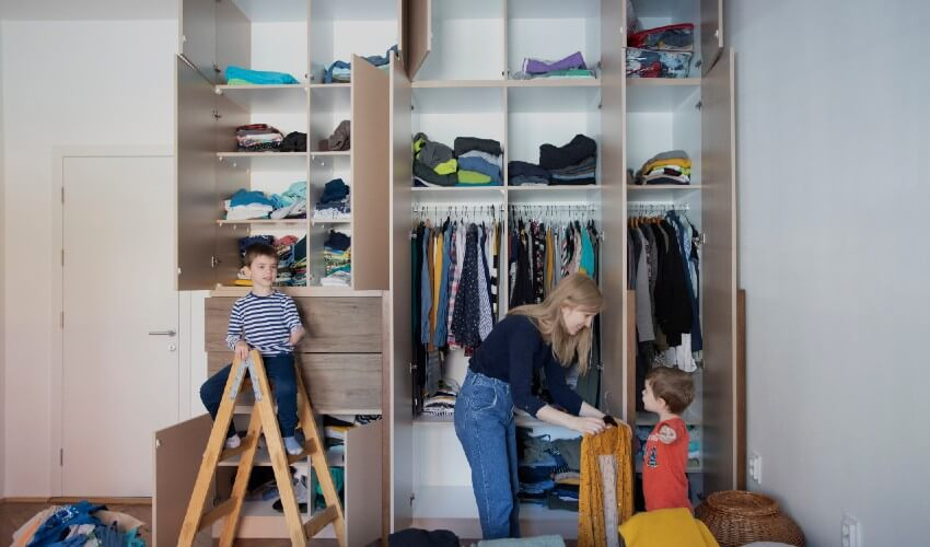 Mom organizing closet with two sons.