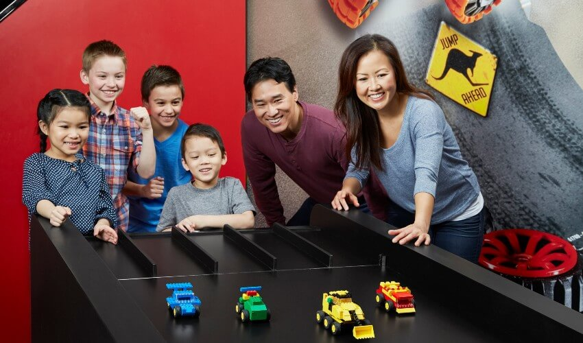 Family racing LEGO vehicles at LEGOLAND Discovery Centre Toronto.