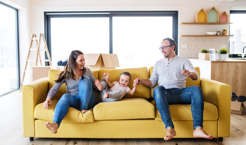 Happy family on a yellow couch.