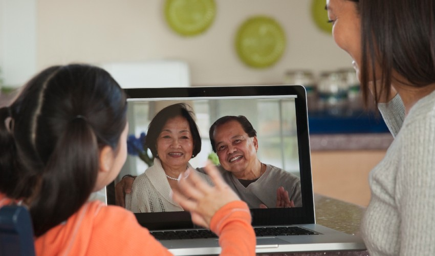 Asian Mother and daughter skyping with grandparents.
