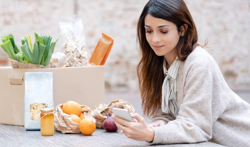 Woman checking her fresh vegetable delivery while holding her mobile phone.