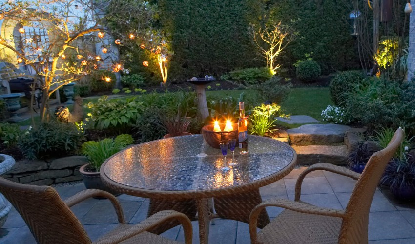 Backyard patio at dusk lit with outdoor lights and electric candles.