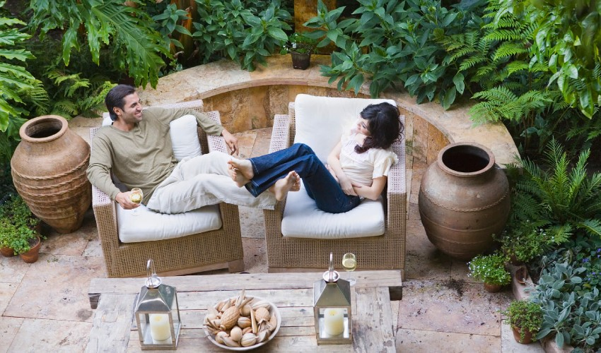 Couple seated on wicker chairs on an outdoor, designer inspired patio