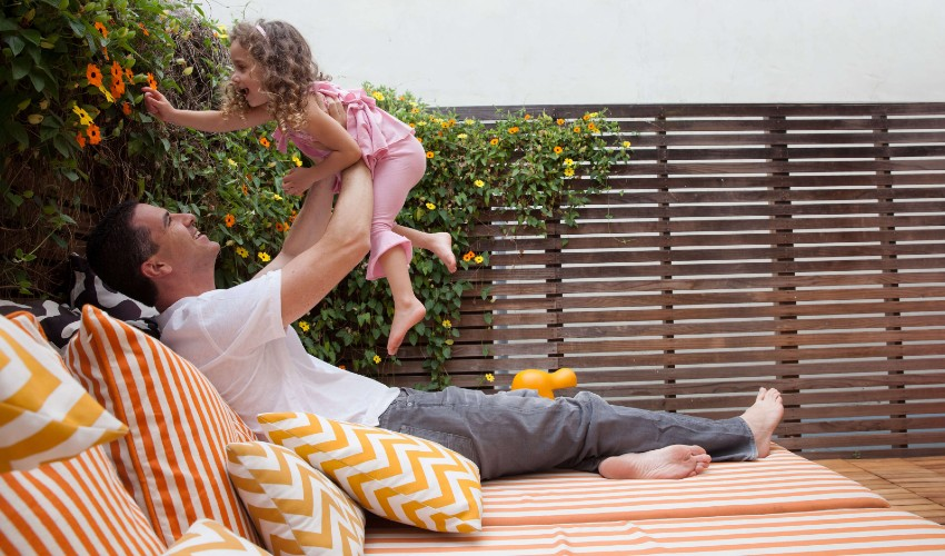 Man and child on backyard patio furniture styled with matching orange and white colour scheme.