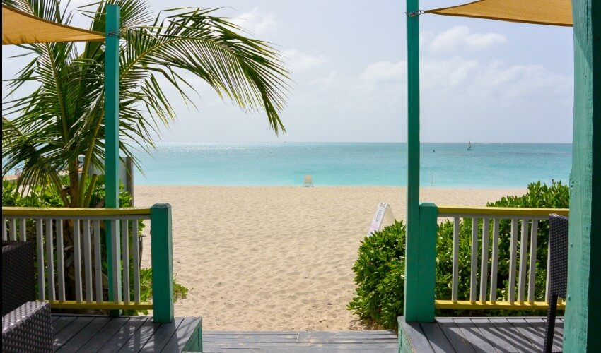 Seaside villa in front of sandy beach and ocean in Turks and Caicos.