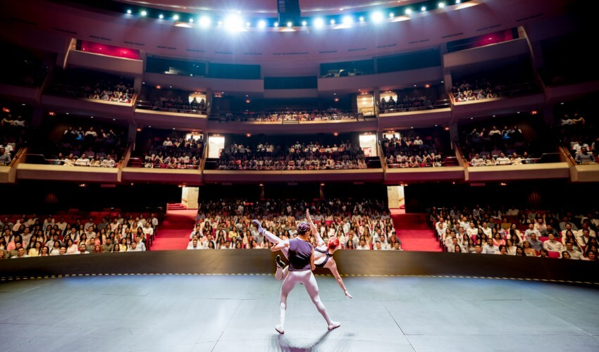 Ballet dancers performing on stage for a large public at a theater.