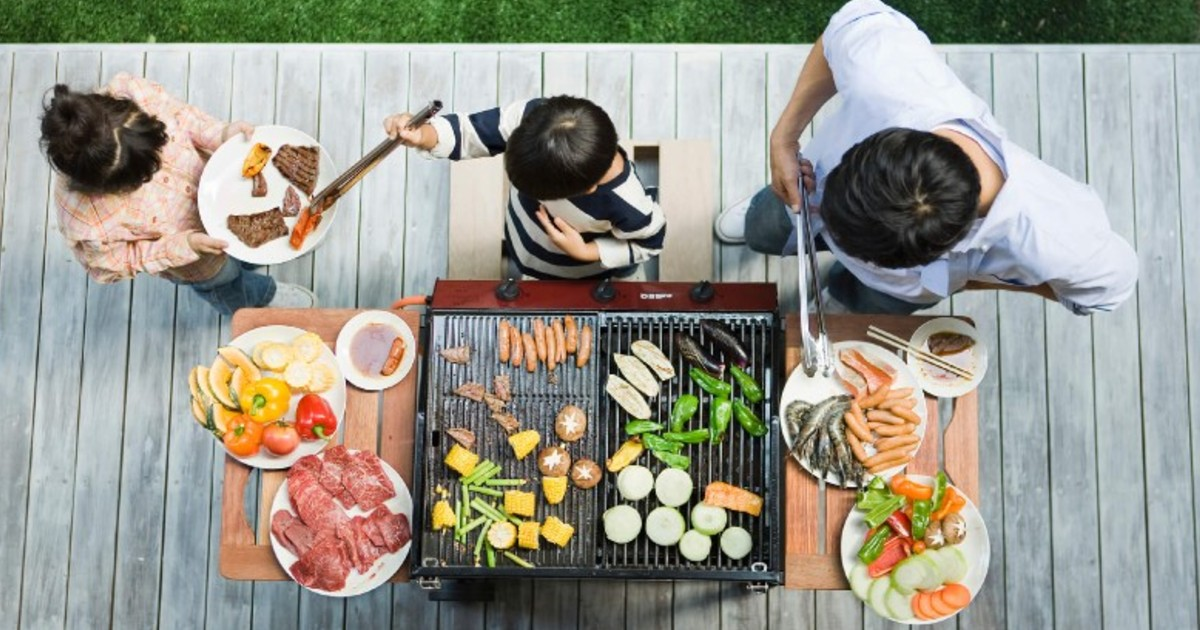 Father cooking on a BBQ surrounded by food and his children.
