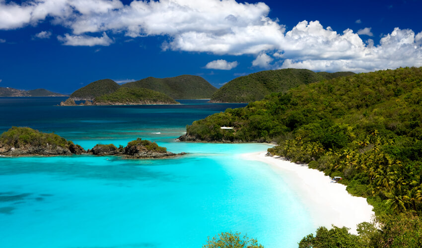 Aerial view of the clear turquoise waters and white sand cove at Trunk Bay Beach in St. John, US Virgin Islands.