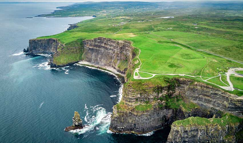 Drone's view of the vibrant green atop Ireland's Cliffs of Moher, with the navy waters of the Atlantic ocean below.
