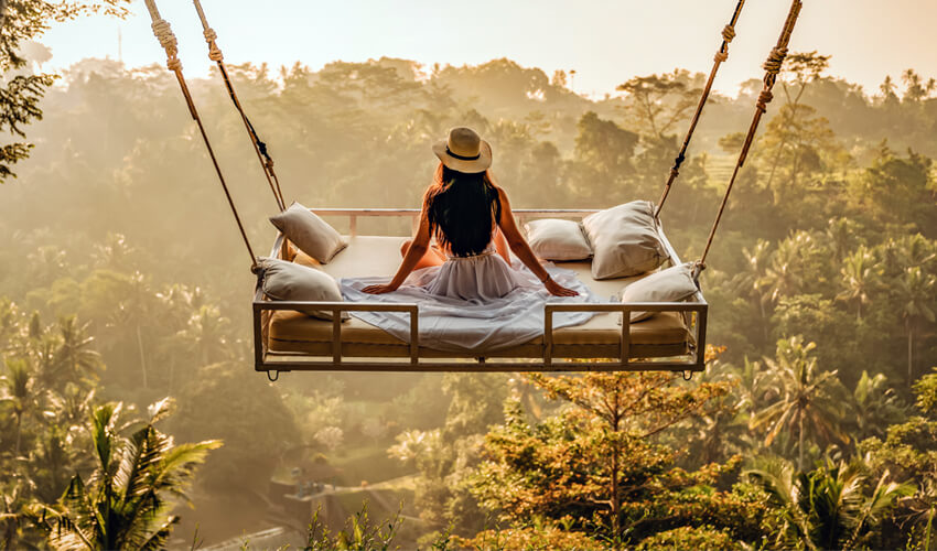 Rear view of woman seated on white suspended bed, as she looks out over sun-drenched jungle.