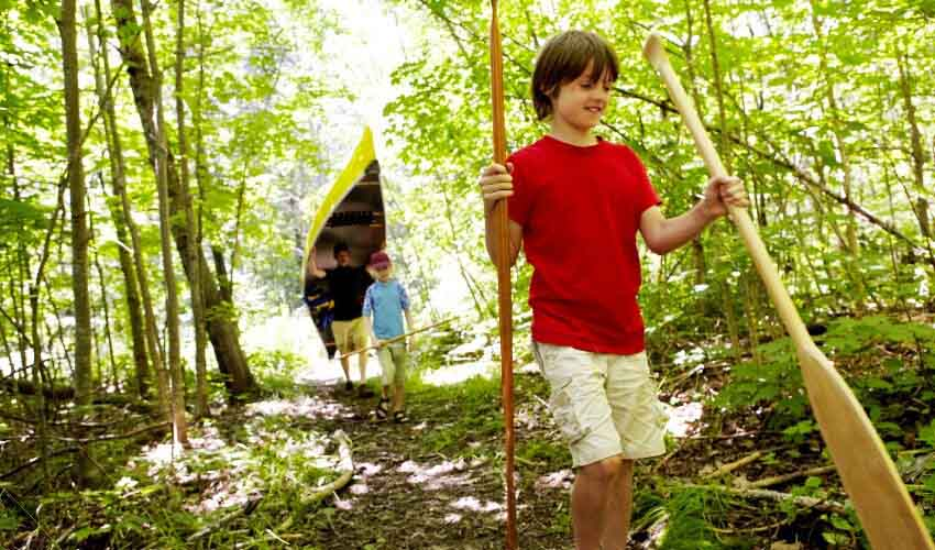 Teenaged boy carrying canoe paddles in forest. Dad and younger boy follow behind carrying yellow canoe and other paddles.