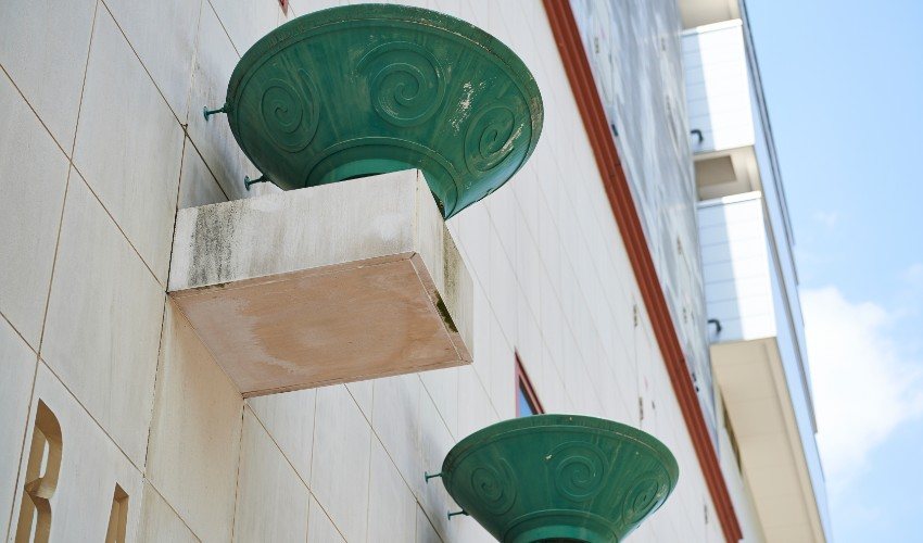 Decorative green ramen bowls perched up on the side of the ramen museum in Japan.