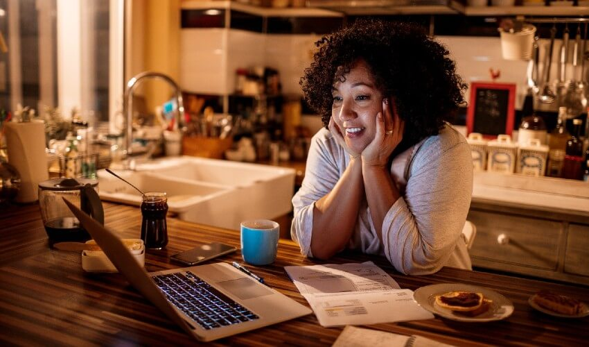 Enthralled woman watching movie on laptop at kitchen counter.