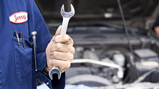 Car mechanic holding a tool