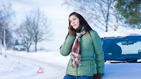 Woman calling for roadside assistance in the winter