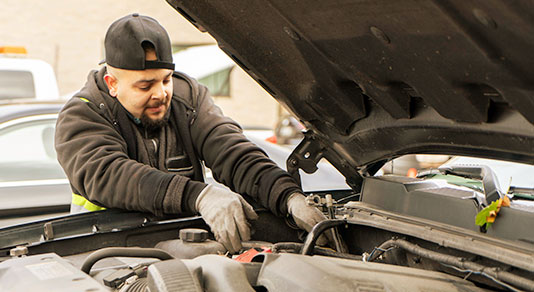 auto mechanic completing car battery check