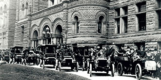 A black and white photo from 1903 showing motorists gathering at Queens Park