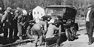 A black and white photo from 1920's showing motorists changing a tire