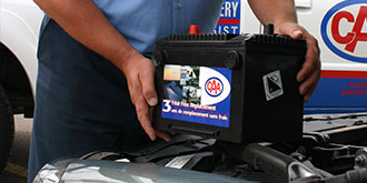 A CAA representative holding a CAA battery on hood of car