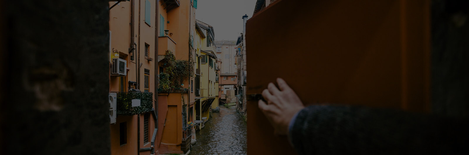 Man opening window and looking at the canal