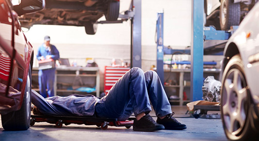 Mechanic under a car in an auto body shop