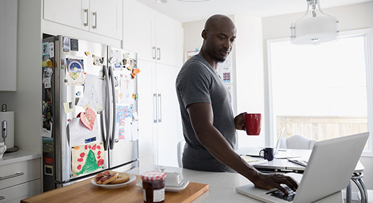Man on his laptop in his kitchen