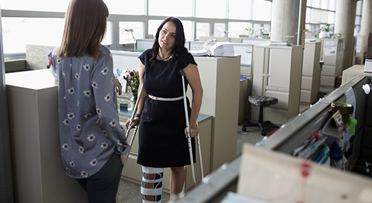 Woman with a broken leg at the office