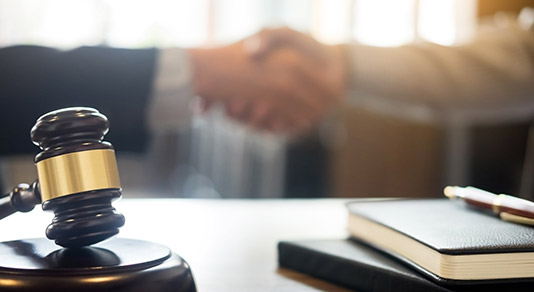 Gavel with two people shaking hands in the background
