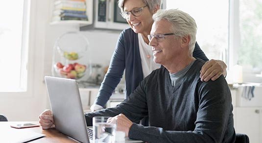 An elderly couple staring at the computer, planning a trip.