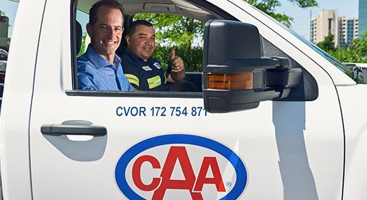 CAA tow truck driver shaking hands with a driver.