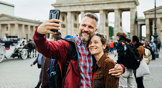 A mature couple taking a selfie in front of Brandenburg Gate in Berlin
