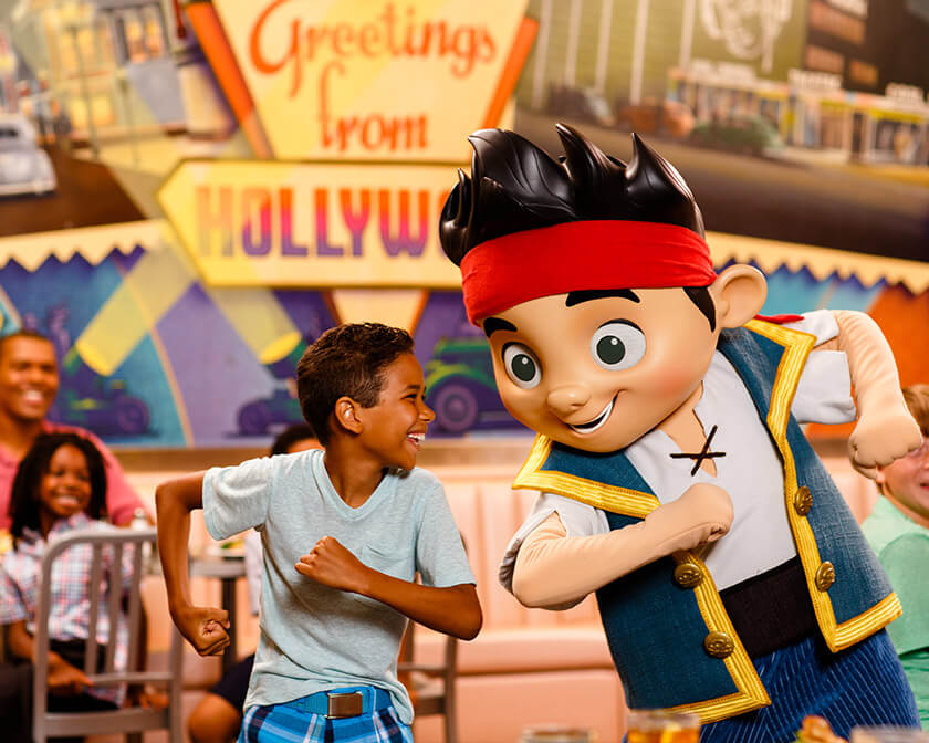 Boy dancing with Jake the Pirate at Disney theme park