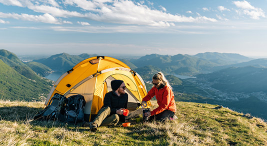Couple camping on mountain top, prepare food and beverages next to tent.