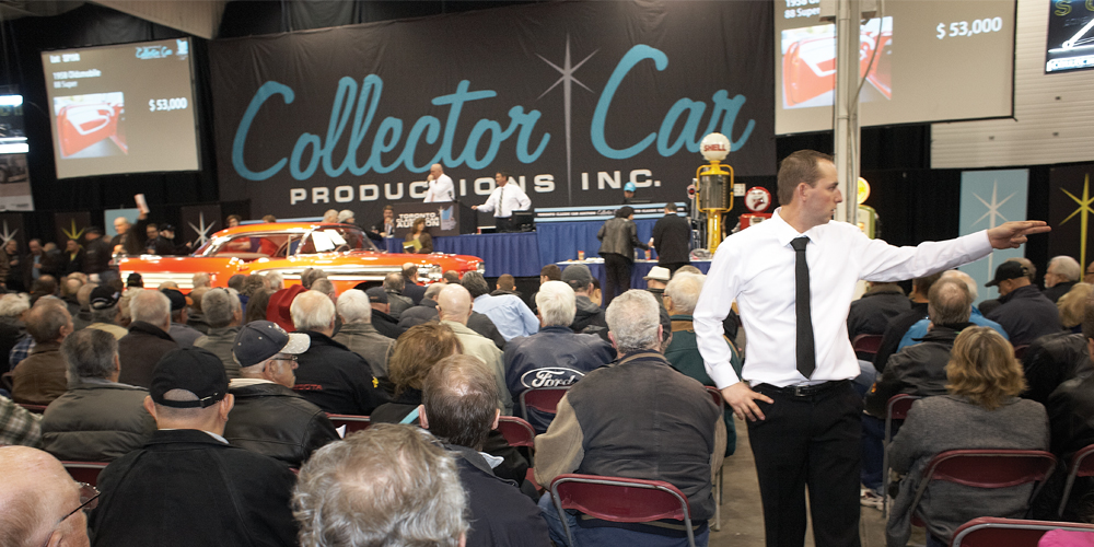 Taking bids from crowd at classic car auction