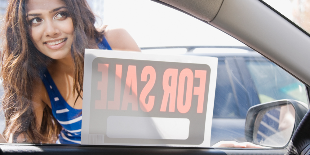 Woman looking in window of car with for sale sign