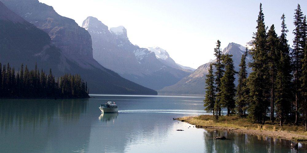 A cruise boat on tranquil Maligne Lake