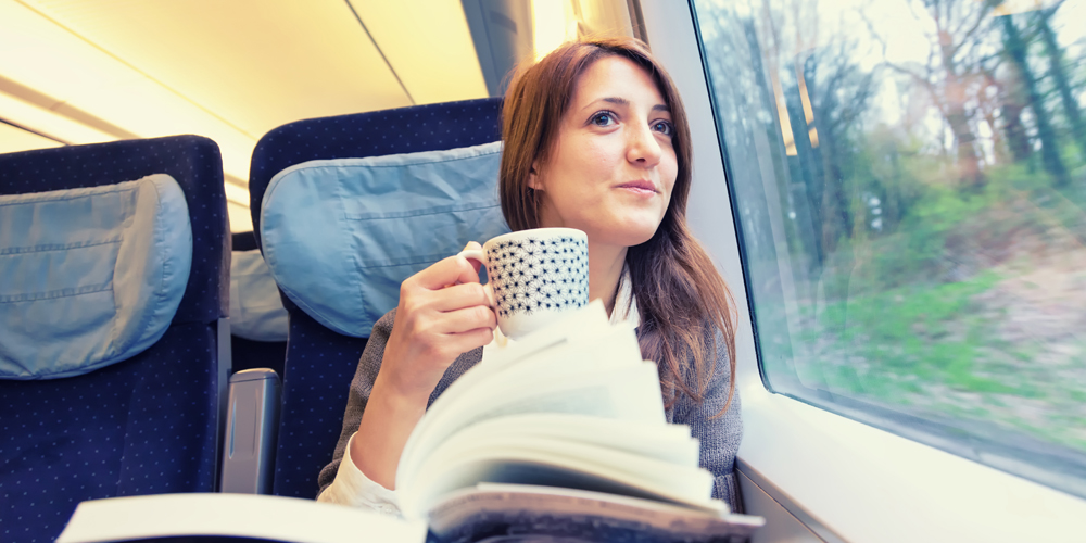 Woman sipping tea and looking out train window