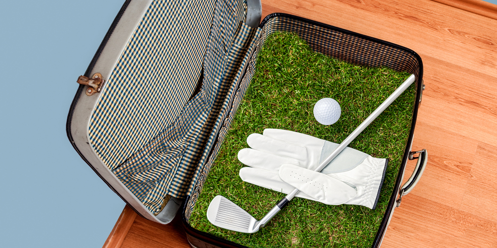 Suitcase open to reveal golf green and golf club